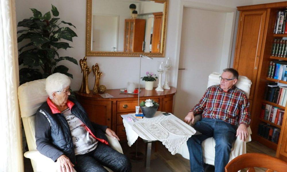 Zwei Senioren sitzen im Wohnzimmer