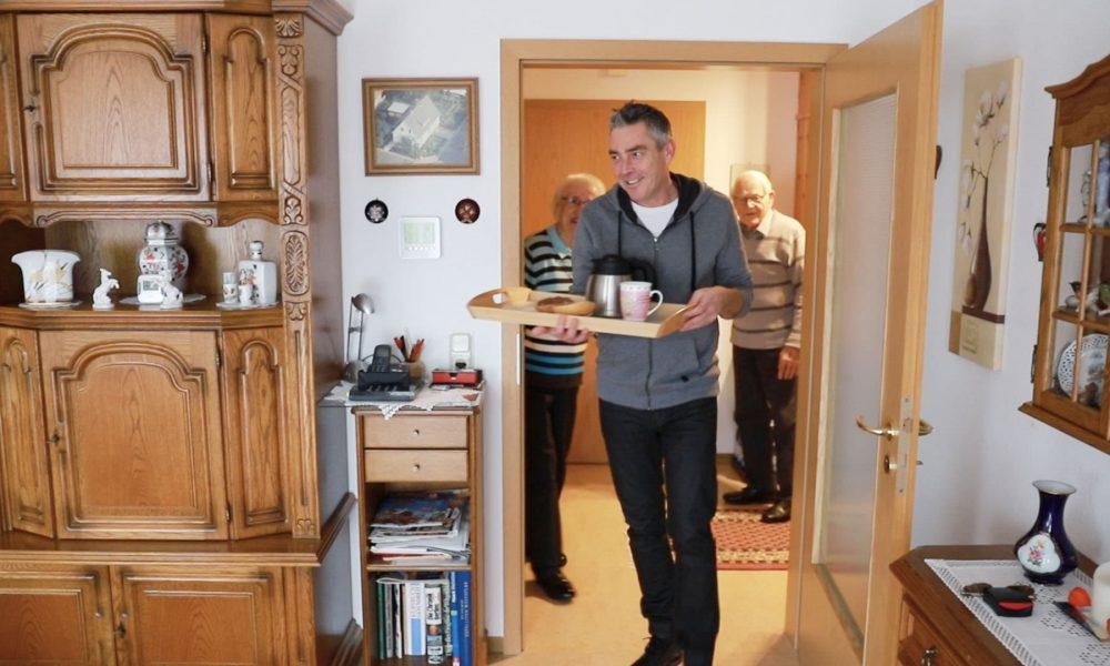 Mann mit Tablett bringt Frühstück